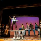 The Scottsboro Boys Company  Centre standing: Kyle Scatliffe (Haywood Patterson)	 Left-right: James T Lane (Ozie Powell), Carl Spencer (Andy Wright), Clinton Roane (Roy Wright), Rohan Pinnock-Hamilton (Olen Montgomery), Emile Ruddock (Willie Roberson), Adebayo Bolaji (Clarence Norris), Idriss Kargbo (Eugene Williams) and Christian Dante White (Charles Weems).  Photo by Richard Hubert Smith.